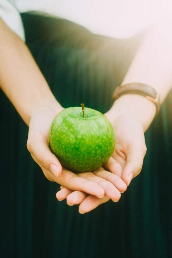 Pomme verte posée au creux des mains- Marie Duval sophrologie