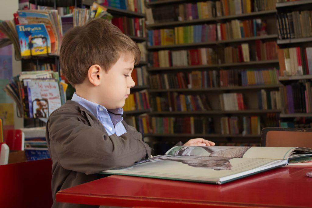 enfant lisant un livre dans une bibliothèque-Marie Duval sophrologue