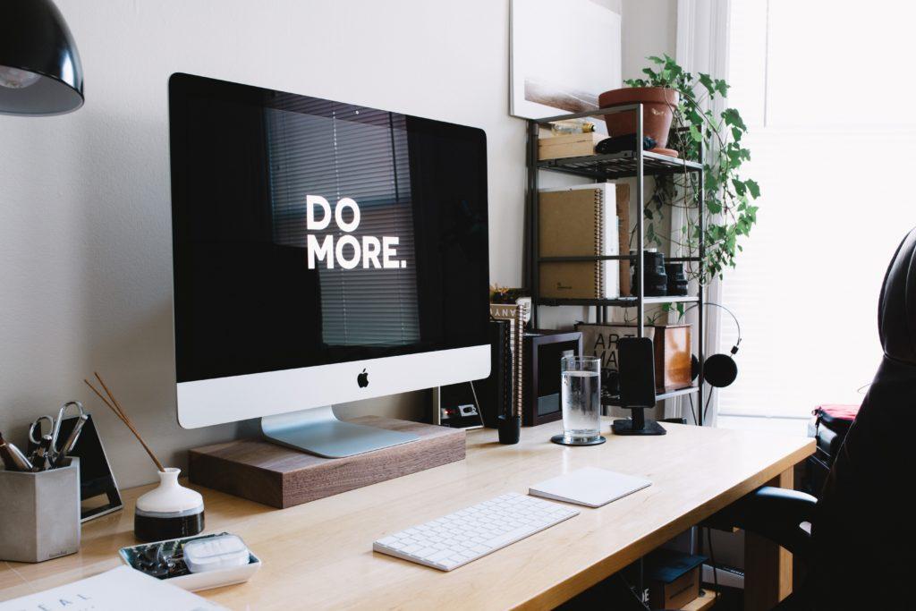 Ordinateur avec l'inscription: DO MORE sur un plan de travail vide