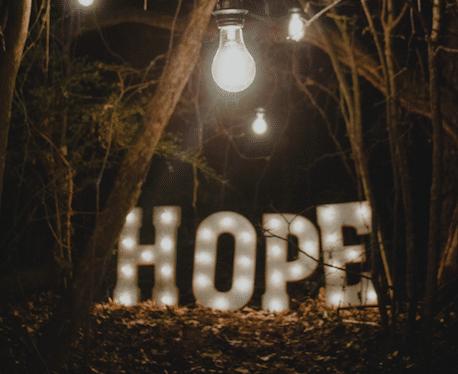Au milieu d'arbres, le mot HOPE écrit en lumière et éclairé d'une ampoule-Marie duval sophrologue